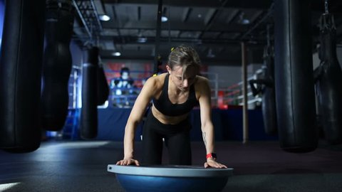 Fit woman in black sportswear doing push UPS on the Bosu and the TRX in gym