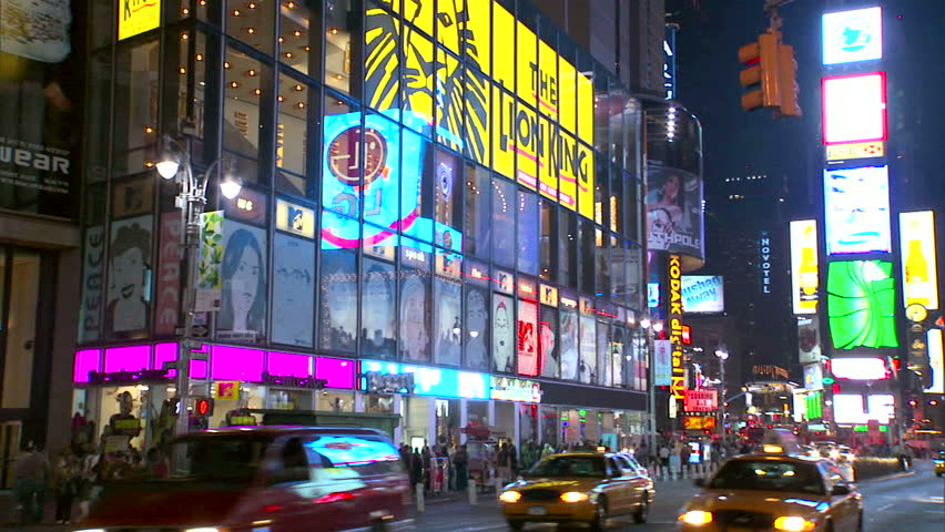 New York, NY - CIRCA 2006: Giant windows, billboards and neon signs surround the gawkers in Times Square at night