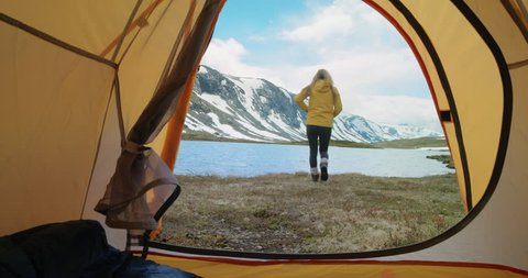 Camping woman climbing out of tent taking photo beautiful lake relaxing on vacation POV Norway