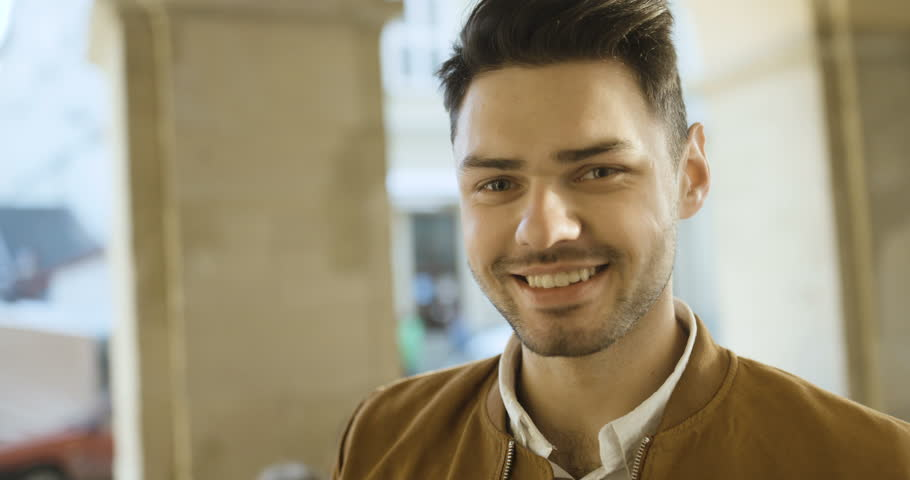 Portrait of handsome young man smiling and looking at camera at sunset on the street | Shutterstock HD Video #25118918