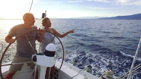 Mature adult couple having good time sailing on a sailboat in the blue ocean on a sunny day on their circumnavigation