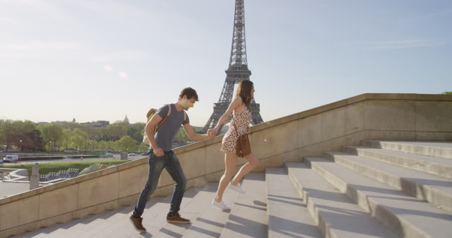 Young couple holding hands woman leading boyfriend walking towards view of Eiffel Tower Paris travel concept