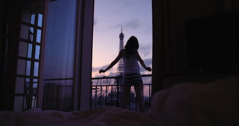 Young tourist woman stretching at sunrise on hotel terrace with view of Eiffel Tower Paris arms raised enjoying european travel adventure celebrating beautiful city