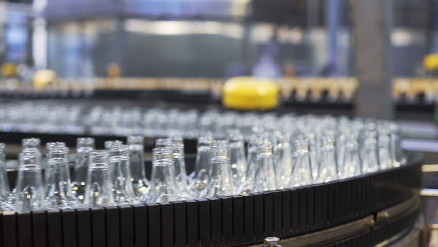 Spill in glass bottles at the plant. Conveyor belt with glass bottles. The production process of alcoholic beverages. close-up