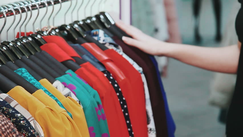 Woman's hands run across a rack of clothes, browsing in a boutique. Woman's hands run across a rack of clothes, browsing in a shop