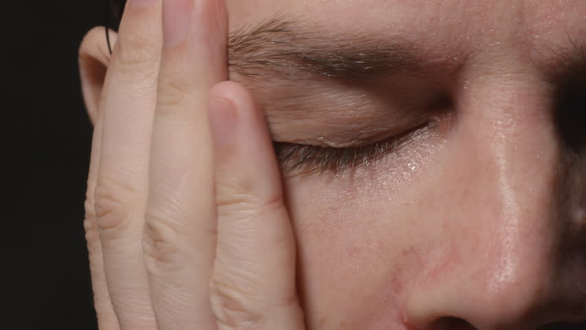 Sweating face on young adult man, who wiped it by hand- Close up
