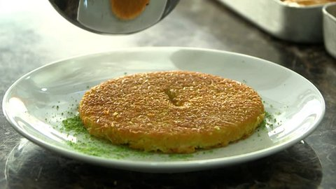 Delicious traditional Turkish kunefe with pistachio on it. Served hot and with syrup. Cooking Kunefe.