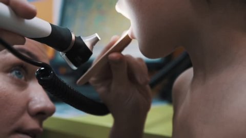 Female pediatrician doctor use otoscope checking little caucasian boy throat, at office during survey close up