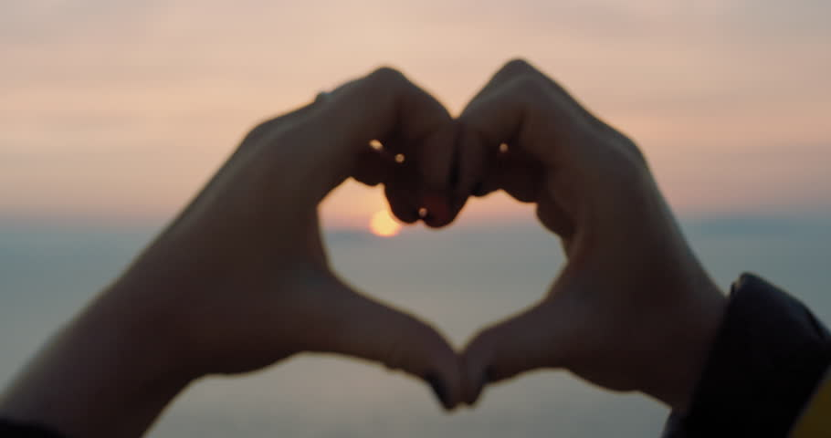 Beautiful Woman making heart shape with hands at sunset Girl holding up love symbol gesture with orange sun flare | Shutterstock HD Video #25165985