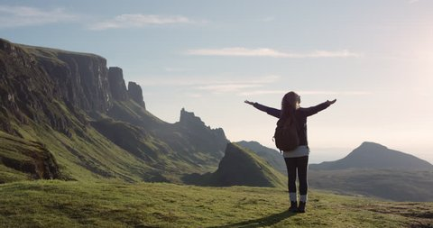 Woman with arms raised on top of mountain looking at view Hiker Girl lifting arm up celebrating scenic landscape enjoying nature vacation travel adventure Quiraing Walk on the Isle of Skye in Scotland