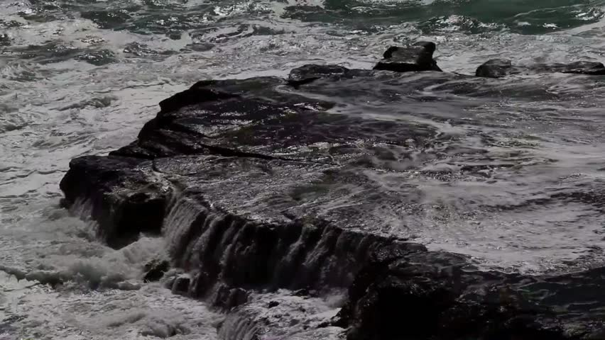 Rough sea washes up flat rocky shore.