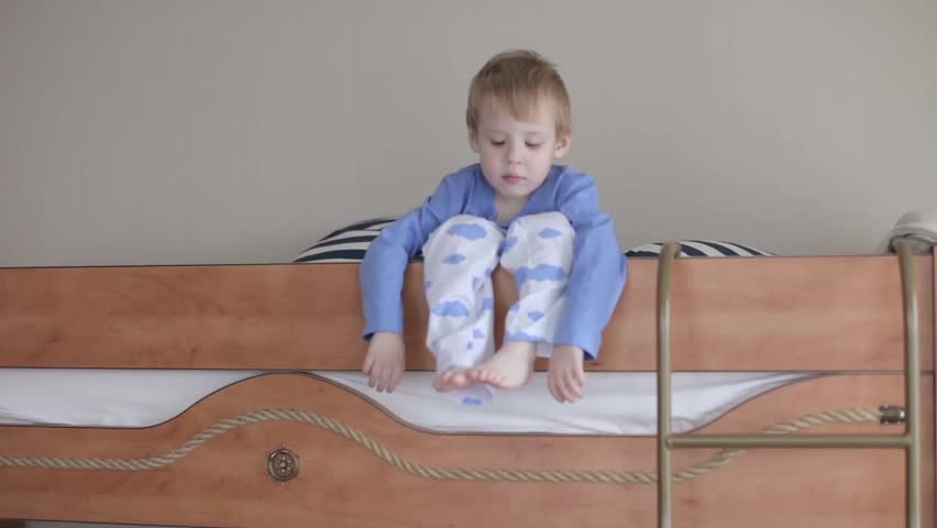 c1f274591fd hd00:15Little Boy in Pajamas Sitting on the Edge of the Bed Dangling ...