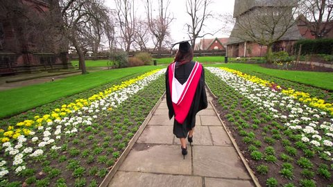 Student on graduation day walking outside university college. Filmed from behind. Attractive Asian young lady. Gown and cap. Old traditional cathedral building, graduate celebrating academic success