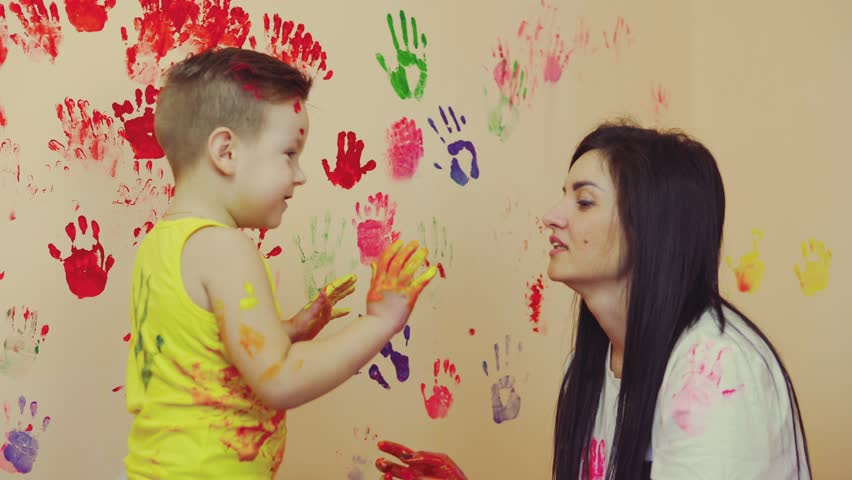 Happy mother and her cute boy having fun together leaving their colorful handprints on the wall. Young happy family. Mother and child concept
