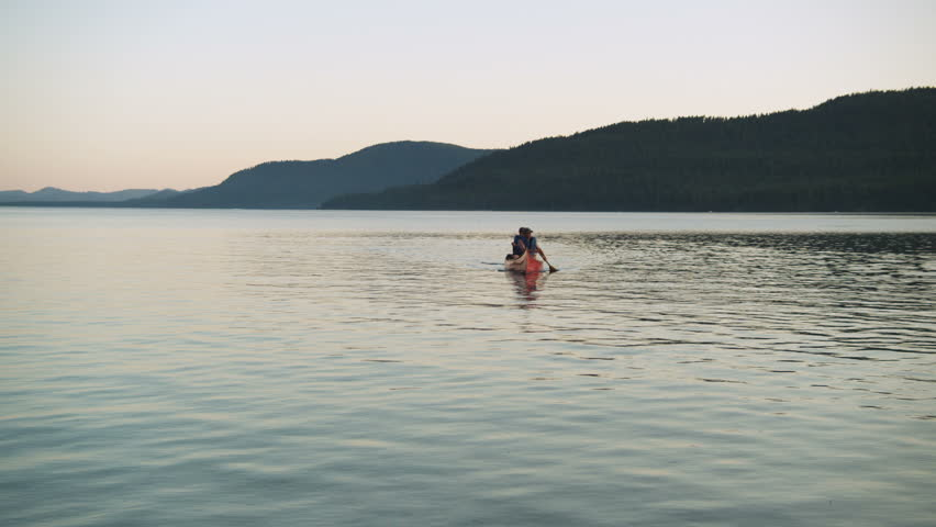 Two men paddle a red canoe across the calm waters of Idaho's Priest Lake.