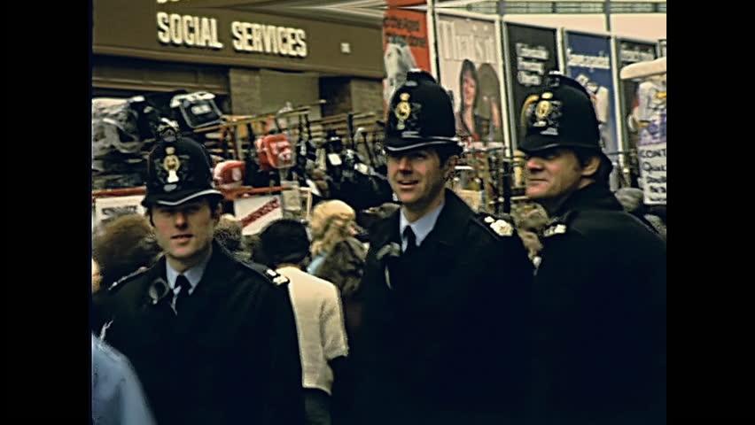 LONDON, UNITED KINGDOM - CIRCA 1979: typical english policemen bobby of London in historic street market Petticoat Lane Market. Historic restored footage on 1970s.