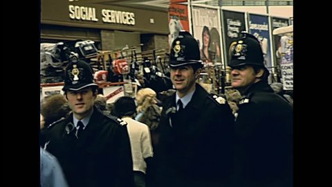 LONDON, UNITED KINGDOM - CIRCA 1979: typical english policemen bobby of London in historic street market Petticoat Lane Market. Historic restored footage on 1970s.