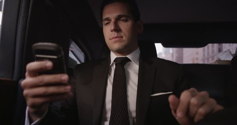 A businessman / executive checks his phone for email or text in the back of a limousine, being driven by chauffeur