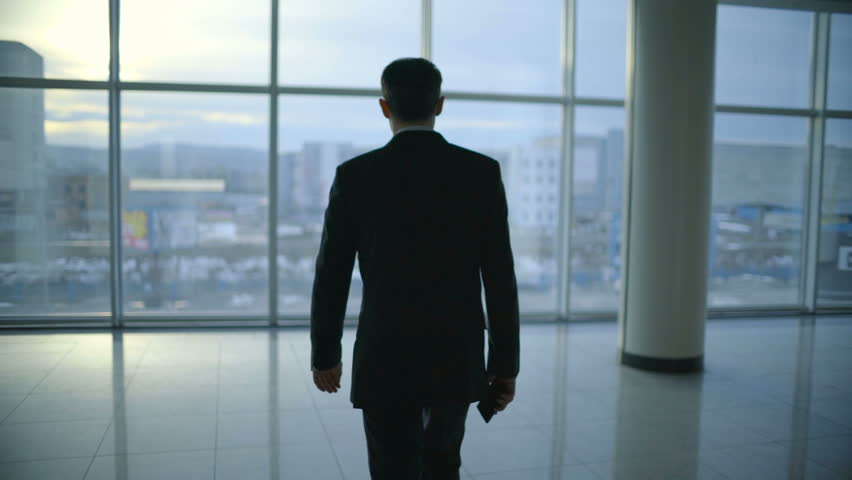 The businessman walk and phone near the panoramic window. Slow motion