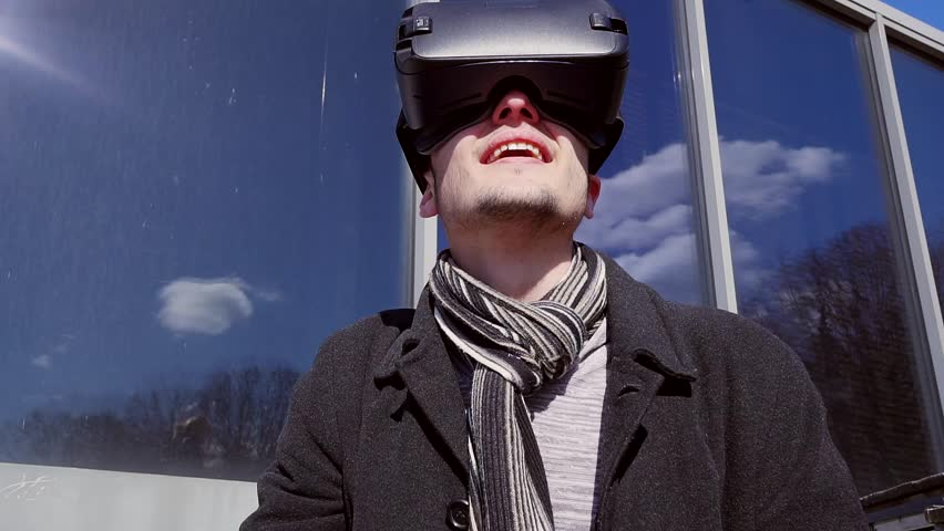 Close-up shot of a man getting experience in using VR-headset. Augmented reality device creating virtual space for smartphone applications