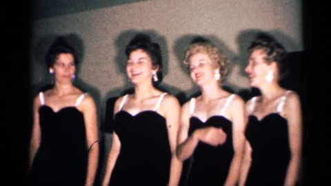 MINNESOTA 1958: four women wearing black dresses sing together holding an object in the right hand.