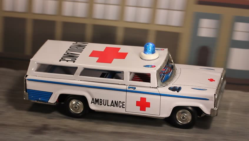 Tin toy Ambulance speeding along a city road with emergency light flashing.