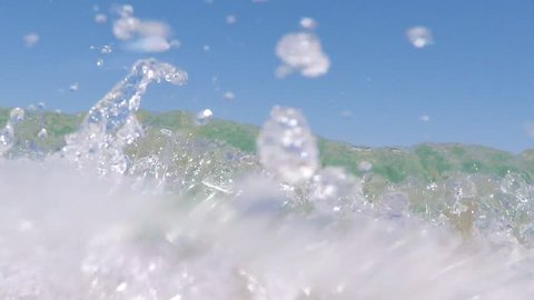 SLOW MOTION: Close up footage of a sea wave splashing the camera or spectator directly.