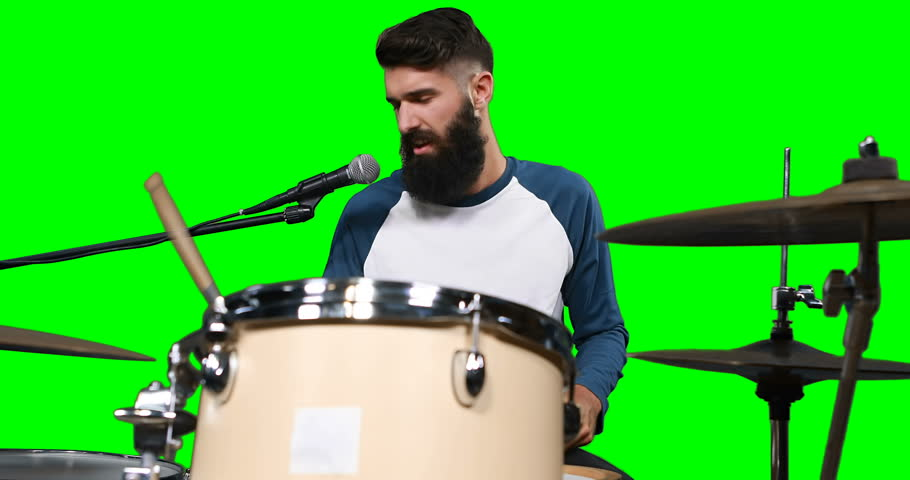 Male drumer playing drum against green screen