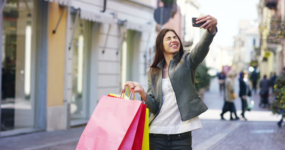 A beautiful woman taking a photo on shopping, and is very happy of their purchases in the period balances. Concept: fashion, shopping, happiness and fashion bloggers.