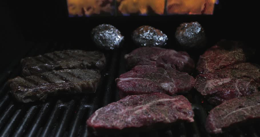 4K video, Cooking of stakes from marble beef on a grill, big pieces of meat with pepper and salt, potato wrapped up in the foil, naked flame, a smoke, a tasty smell, canon Eos 1dx mark ii