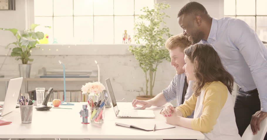 Track across table in casual sunny startup office with young happy adults. Raw version available on request | Shutterstock HD Video #25328312