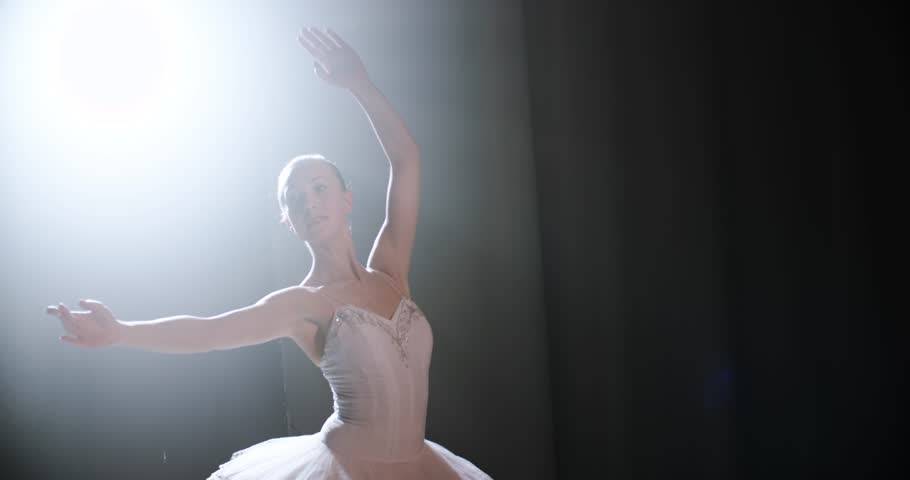 A graceful ballerina dancing ballet elements in the dark with light and smoke on the background, slow motion