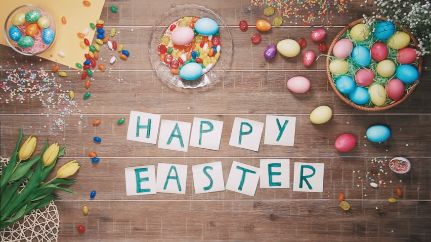 Man put words Happy Easter on table decorated with easter eggs. Top view | Shutterstock Video #25343030