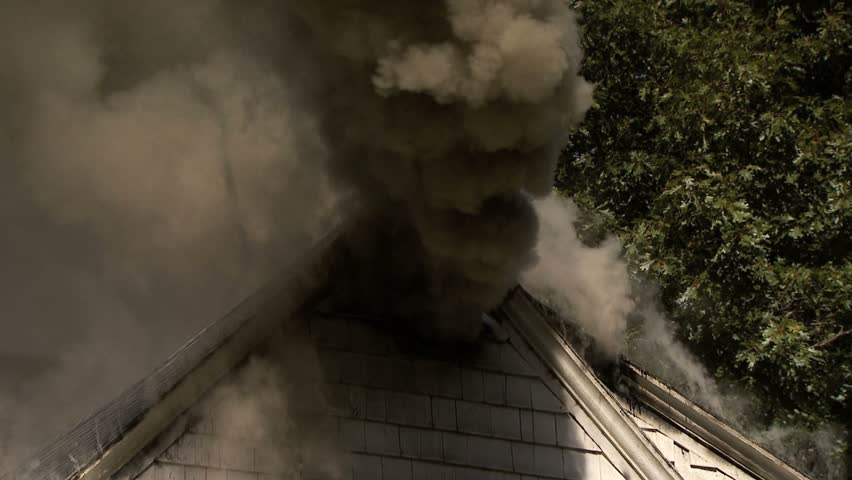 Smoke pouring out of attic vents of house on fire