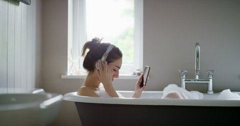 Beautiful Woman listening to music in bathtub enjoying relaxing bubble bath lifestyle real natural body care