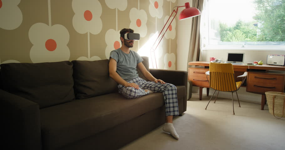 Young man wearing virtual reality headset sitting on sofa at home watching 360 video imagination concept | Shutterstock HD Video #25379108