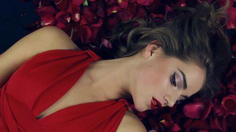 Girl in red dress with beautiful hairdo lies in petals red roses,slowly turns head from the side, hands touch her face.Valentine's Day.Girl in love.Red lipstick and bright makeup.Background of flowers