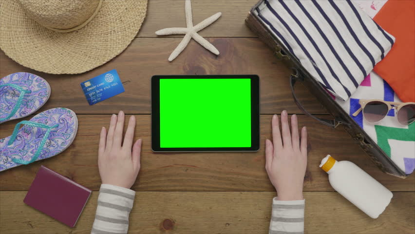 Overhead lockdown footage of woman touching digital tablet with green screen on wooden table. Aerial flat lay of beach supplies with passport and credit card on wood. Female is preparing for vacation.