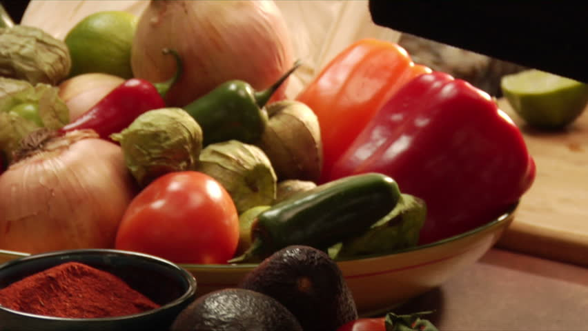 vignette of pans over mexican vegetables, serving and garnishing guacamole