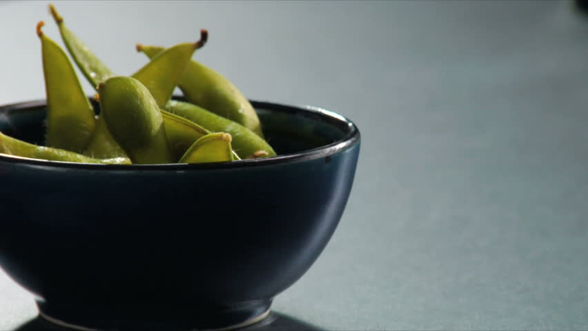 Lock down shot of salt being sprinkled on hot Edamame (soy beans). | Shutterstock HD Video #2540978