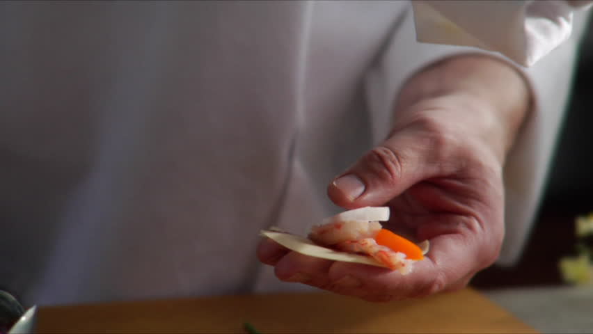 Chef prepares Asian shrimp appetizer and camera pan over as he places it on a serving plate.