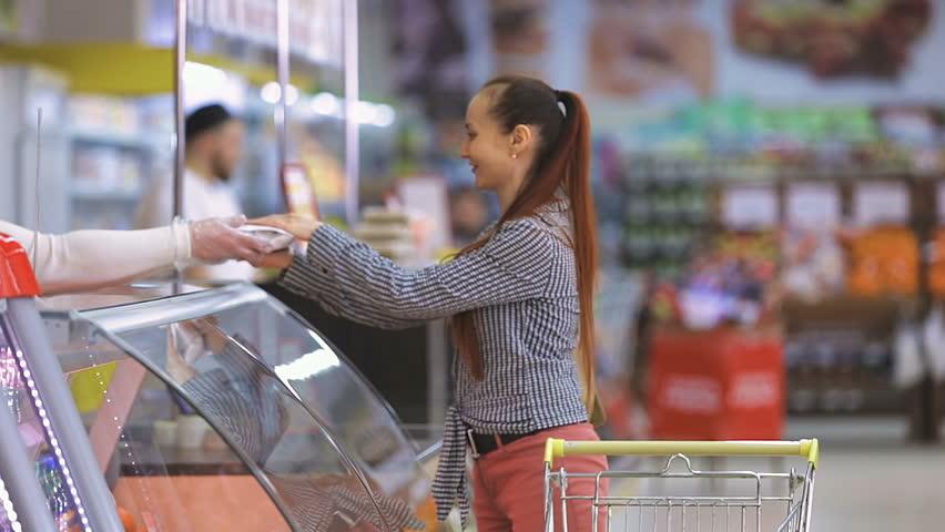 A woman buys food near a glass window in a supermarket | Shutterstock HD Video #25443158
