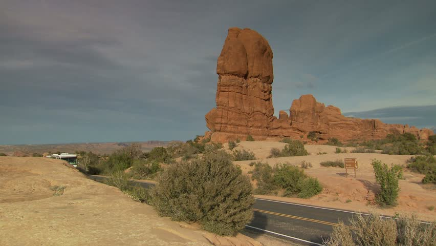 RV driving past Balanced Rock formation at Arches