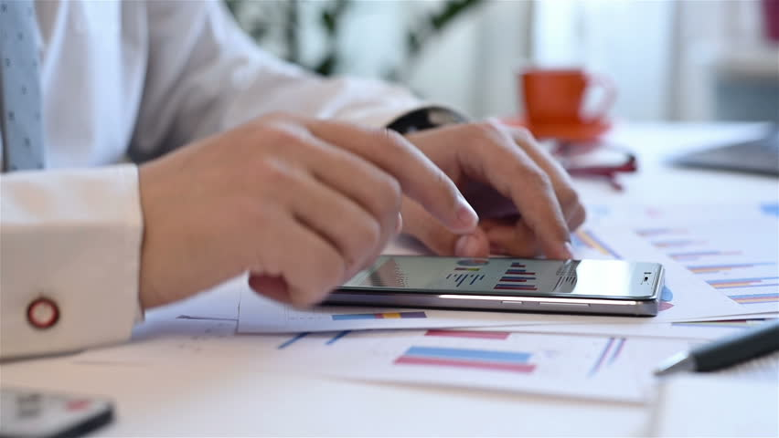 Businessman Using Mobile Phone With Growth Graph Chart And Stacks Data, | Shutterstock HD Video #25452161