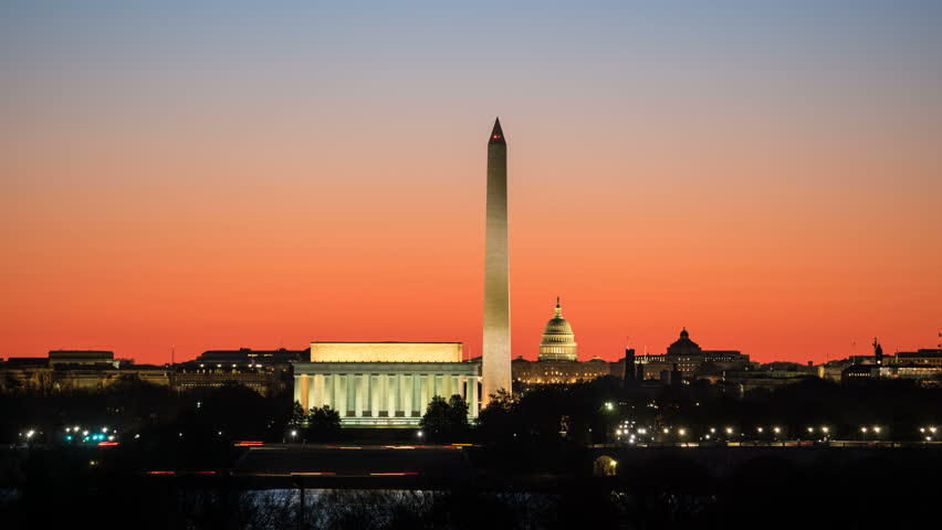 (Time-lapse/Zoom-in) National Mall attractions including the Lincoln Memorial, Washington Monument and US Capitol building as the orange pre-sunrise sky begins to lighten in Washington, DC.
