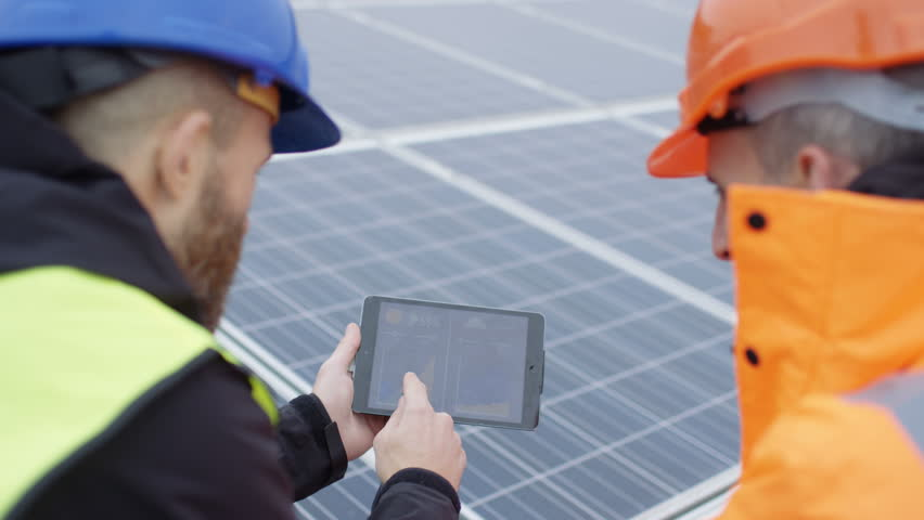 4K Technicians with tablet checking the panels at solar energy installation