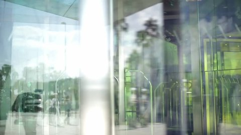 People using automatic revolving glass door or entering rotating spinning glass doorway. Entrance to the hotel,business ,exhibition or shopping center. People silhouettes and their reflection.