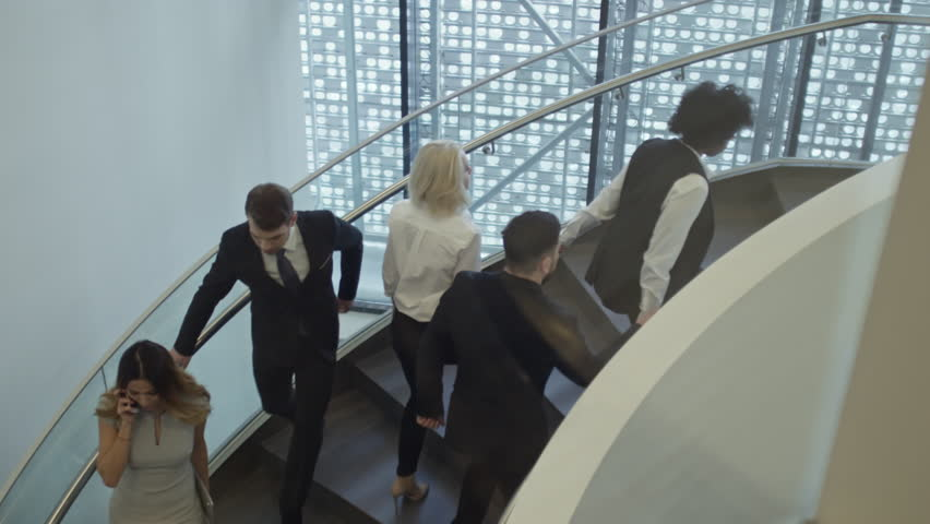 High angle view of businessmen and businesswomen walking up and down the stairs in office building. | Shutterstock HD Video #25518668