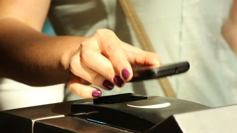closeup  female hand with manicure bring the phone to  ntfs system reader in metro turnstile for payment of fare