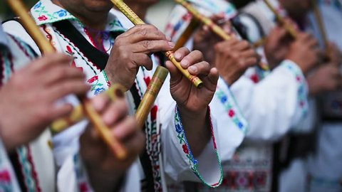 People in romanian traditional costumes singing at wooden flutes
